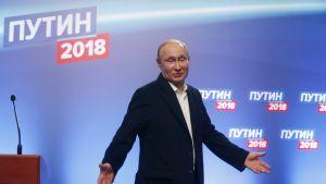 Vladimir Putin puku yllään, levittelee käsiään.