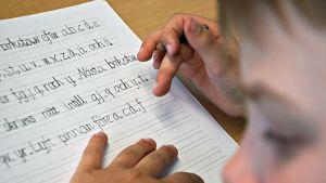 Koululainen ruotsinkielisen kielivihkon äärellä.