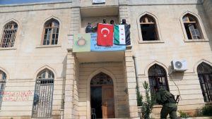 Mies juoksee kohti kivistä hallintorakennusta, jonka parvekkeelta miesjoukko roikuttaa Syyrian ja Turkin lippuja.