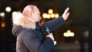 Presidentti Putin tervehtii kannattajiaan vaalivoiton jälkeen Kremlissä.