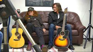 Pelle Miljoona ja Hapa Tyni treenikämpällä Haminan keskustassa, miehet istuvat sohvalla kitaroiden kämpässä treenikämpällä