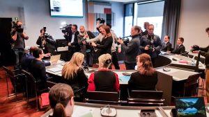 Lehdistö oikeussalissa ennen oikeudenkäyntiä