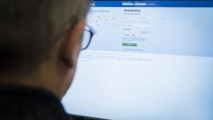 Mies tietokoneen ääressä kirjautumassa Facebookiin.