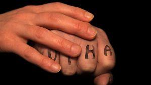 Vihainen nyrkki, jonka päällä rauhoittava käsi.
