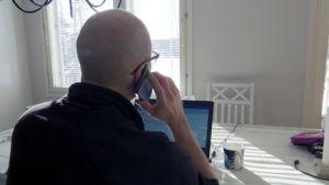 Mies tekee läppärillä etätöitä kotona keittiön pöydän ääressä ja puhuu kännykkään