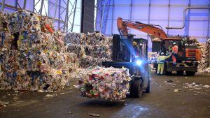 Kuva Fortumin muovinjalostamolta, jossa trukki kuljettaa kierrätysmuovipaaleja.