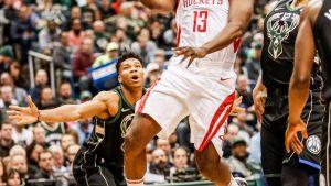 James Harden heittää kahden Milwaukee-pelaajan välistä.