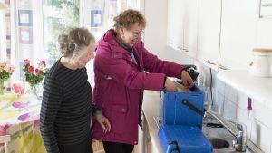 Kaksi naista ottaa vakuumipakattuja ruokia kylmälaukusta.
