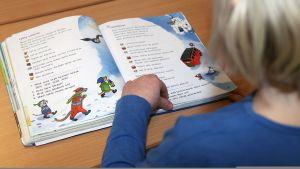 Lapsi lukee oppikirjaa koulussa.