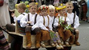 Lapsia kansallispuvuissa katujuhlassa.