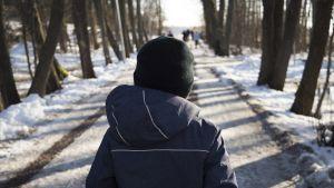 Lapsi kävelee kävelyreitillä luonnossa.