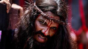 Intian kristitty pukeutuneena Jeesus Kristukseksi orjantappuraseppele päässä kantaa ristiä.