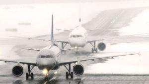 Aeroflotin ja Finnairin koneet lumipyryssä Helsinki-Vantaan lentokentällä.