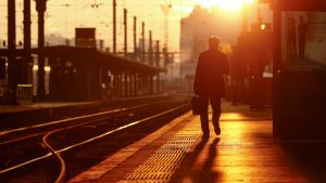 Yksinäinen mies auringonnousun aikaan tyhjällä junalaiturilla.