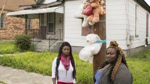 Tanesha Bates (vas.) ja Raven Starks (oik.) Taneshan kotikadulla paikassa, johon paikalliset asukkaat tuovat nalleja ja nauhoja kuolleen teinitytön muistoksi.