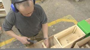 Mies työstää puulelua.