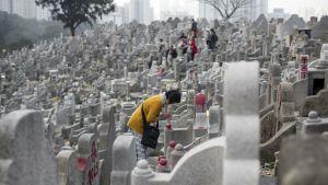 Nainen rukoilee haudalla Hongkongissa.