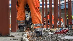 Työmiehiä rakentamassa Jyväskylän poliisaitalon putkaa takapihalle.