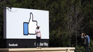 Mies seisoo suuren Facebook-kyltin edessä ja näyttää peukaloaan toiselle miehelle, joka ottaa kuvaa.