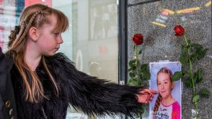 nainen katsoo seinään kiinnitettyä kuvaa