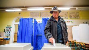 mies laittaa vaalilipun uurnaan