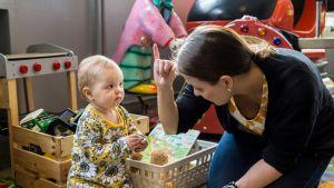 Äiti ja 1-vuotias vauva kommunikoivat viittomalla.