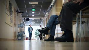 Asiakkaat jonottavat terveyskeskuksen käytävällä.