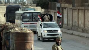 Kaksi bussia kulkee kadulla. Niiden edellä ajaa lavakuorma-auto, jonka lavalla istuu selkä menosuuntaan maastopukuinen mies. Autossa on neljä Syyrian lippua.