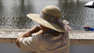 Nainen katselee kun ihmiset kalastavat Coruchessa Portugalissa.