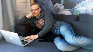 Juha-Matti Jääskelä käyttää kannettavaa tietokonetta sohvalla loikoillen.