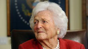 Barbara Bush kasvokuva. Pukeutunut punaiseen jakkuun ja helmikaulakoruun.