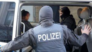 Epäilty istuu poliisiautossa. Poliisi seisoo pakettiauton takaovella.