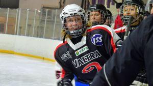 Jääkiekkoa pelaavia naisia vaihtoaitiossa.