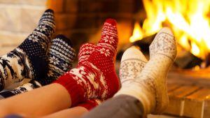 Perheenjäsenet lämmittelevät jalkojaan takkatulsen ääressä