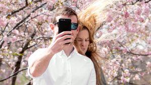 Nuoripari poseeraa älypuhelimen kameralle.