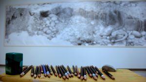 Etualalla lyijykyniä ja taustan seinällä suuri lyijykynäpiirros