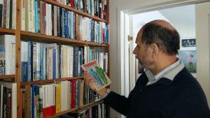 Kirjailija Joni Skiftesvi katsoo esikoisteostaan Puhalluskukkapoika ja taivaankorjaaja kirjahyllyn ääressä.
