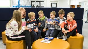 Kuvassa uutisluokan Aapo Sillanpää istuu koulukavereidensa keskellä ja haastattelee heitä.