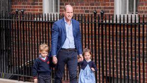 Prinssi William taluttaa kahta lastaan kdulla