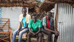 Kolme nuorta entistä lapsisotilasta yhdessä peltimajan ulkopuolella Etelä-Sudanissa.