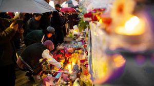 Ihmiset tuovat kukkia ja kynttilöitä surmapaikalle Torontossa.