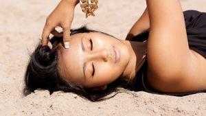 Nuori nainen makaa hiekalla.