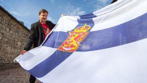 Kimmo Kiljunen pitelee ensimmäistä Suomen lippua