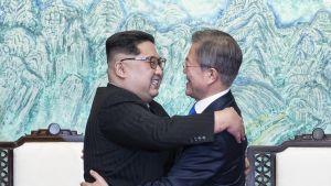 Kim ja Moon halaavat hymyillen kokoushuoneessa. Kimillä on musta maolaishenkinen puku ja Moonilla tummansininen puku.