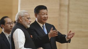 Harmaahiuksinen mies ja musta hiuksinen mies jolla vaalean sininen kravatti, seisovat rinnakkain. Takana silmälasipäinen mies.