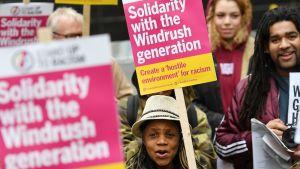 Hattupäinen nainen pitelee kylttiä, jossa lukee fuksianvärisellä pohjalla solidaarisuutta Windrush-sukupolvelle.