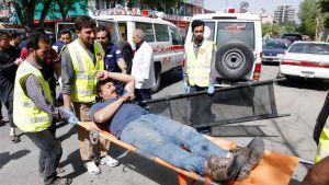 Pommi-iskussa loukkaantunutta kannettaan hoitoon Kabulissa.