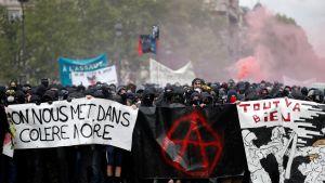 Mustiin pukeutuneita mielenosoittajia rivissä banderolleineen. Taustalla punaista savua.