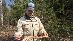 Jannu Pajula tutkii karhun tekemiä tuhoja mehiläistarhallaan