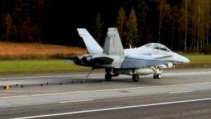 Ilmavoimien Hornet harjoitteli pysäytysvaijerilaskua Lusin maantiekentälle sotaharjoituksissa 2016.